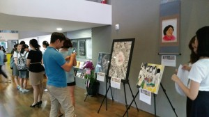 'Justice for Comfort Women' members' paintings are exhibited at the lobby of the National Theater. People taking pictures.